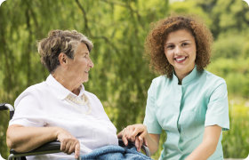 elder woman smiling to her caregiver